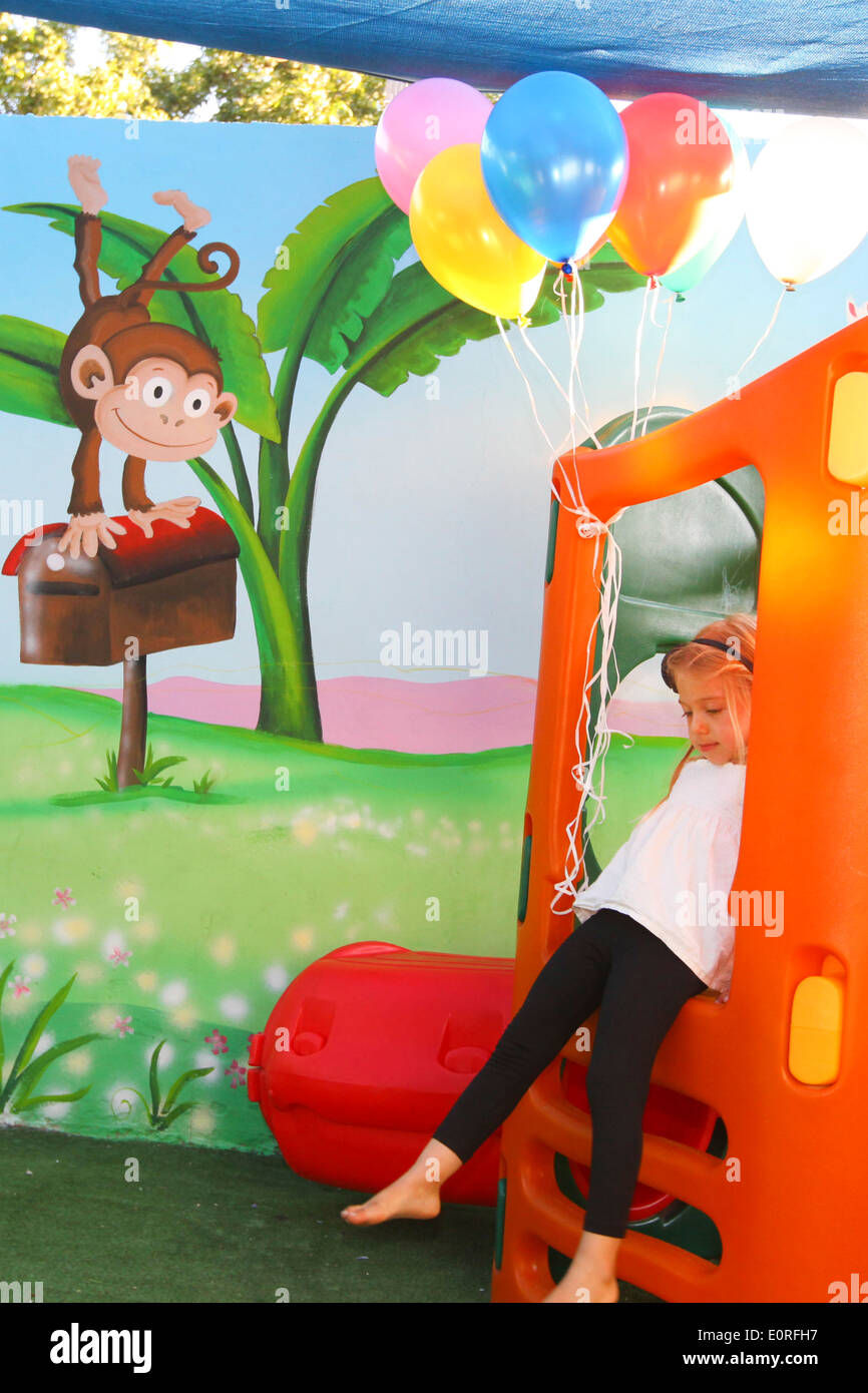 Young girl plays in a kindergarten playroom. Model Release Available - Stock Image