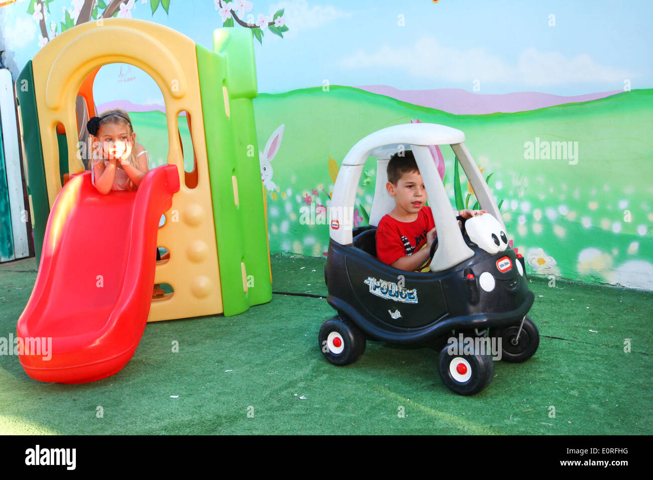 Young girl and boy play in a kindergarten playroom - Stock Image