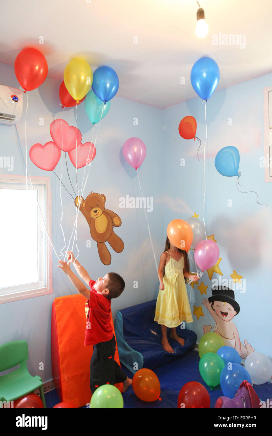 Young girl and boy play with balloons in a kindergarten playroom - Stock Image