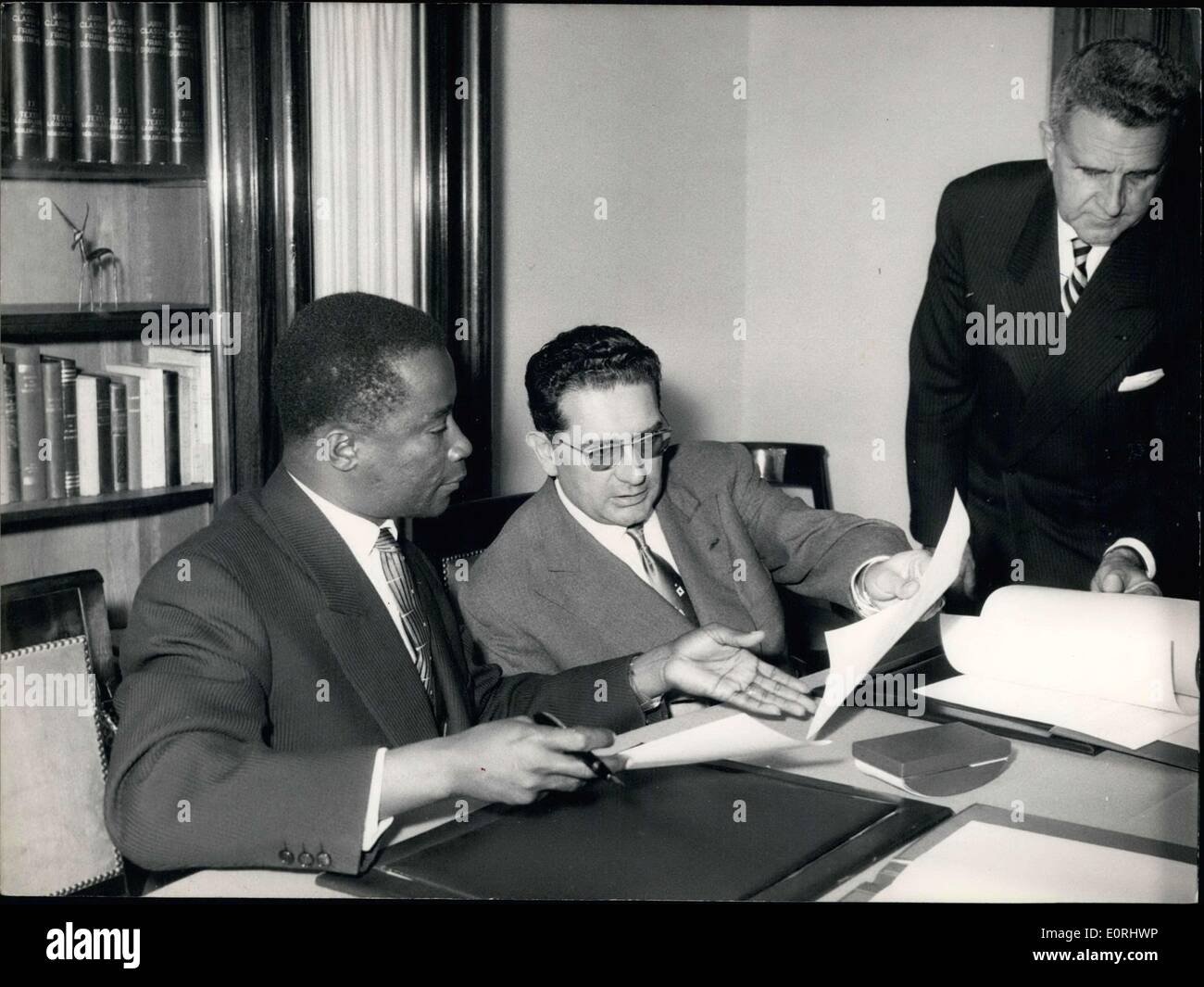 Sep. 14, 1959 - The Convention of Cooperation with Tchad was signed this morning at the new seat of the OCRS in Paris. Soustelle, a general delegate of the OCRS, and Lisette, the Vice-Prime Minister of Tchad, were in charge of the economic coordination, planning, and the external relations, and are pictured signing the agreements. Faure, a representative of the French Prime Minister, is standing behind them. - Stock Image