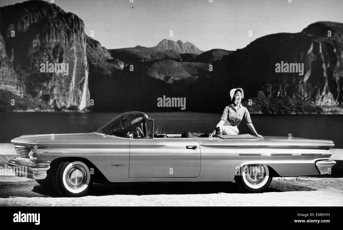 Model posing with a 1960 Pontiac Bonneville Convertible - Stock Image