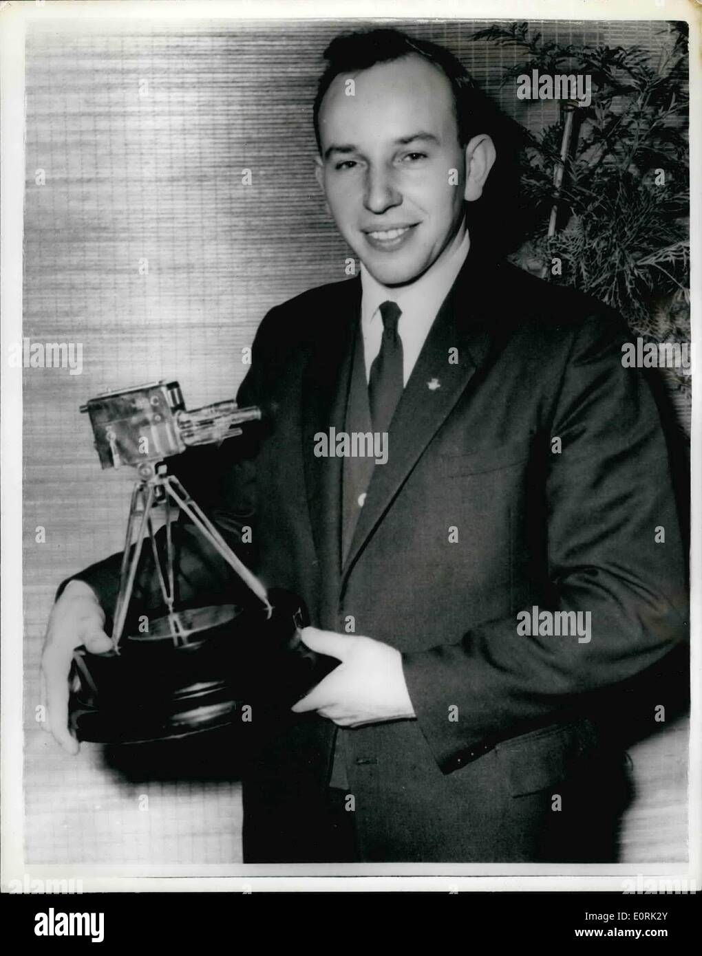 Dec. 12, 1959 - John Surtees is chosen as TV's Sportsman of the year: John Surtees, the fastest man in the world on a motor-cycle, was last night chosen to Sports Personality of 1959 by B.B.C. Television's Sportsview Surtees, world motor-cycling champion for the second year in succession, was presented with the trophy a miniature television camera by Sir John Hunt, of Everest fame. Photo shows John Surtees the fastest man in the world a motorcycle pictured with his trophy after the presentation last night. - Stock Image