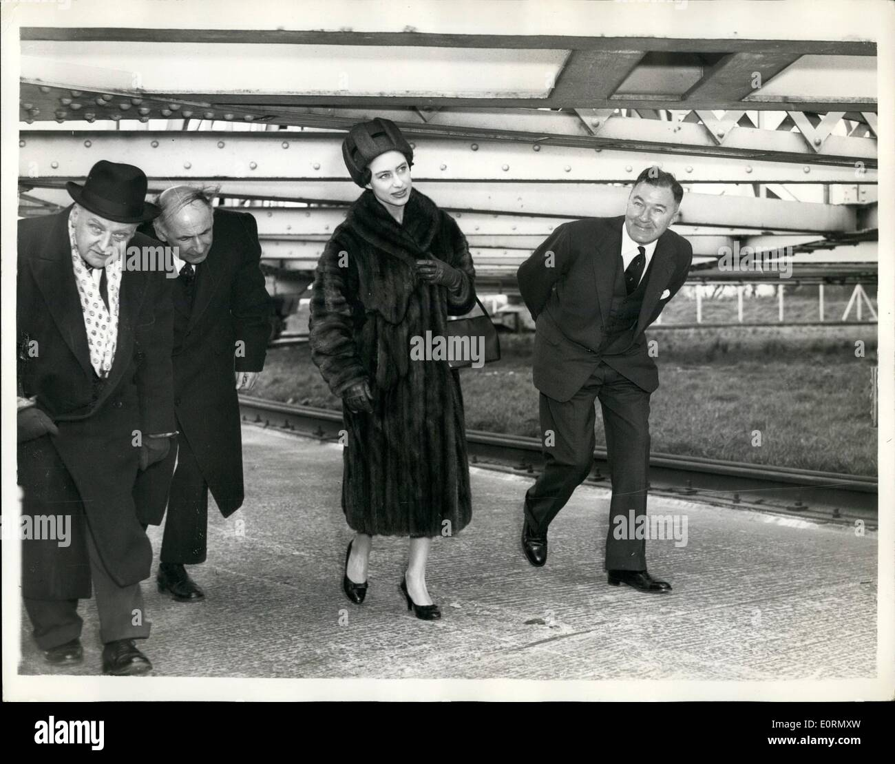 Mar. 03, 1960 - Princess Margaret Visits Jodrell Bank Radio Telescope: H.R.H. Princess Margaret this morning paid a visit to Jodrell Bank Radio Telescope where she listened to recordings of the signals transmitted by the newes American satellite - Pioneer V. Photo shows Princess Margaret seen ducking with other members of the party - beneath one of the wheel cradles of the giant telescope - at Jodrell Bank today. - Stock Image