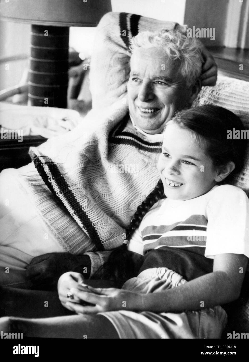 Actor Charlie Chaplin watching television with his daughter Geraldine - Stock Image