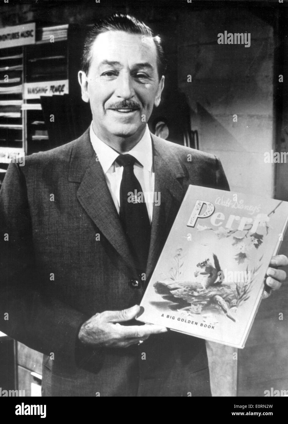 Walt Disney holding up one of his story books - Stock Image