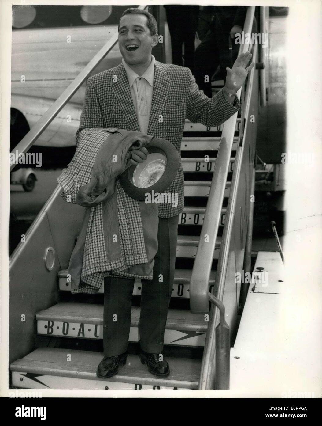 Apr. 16, 1960 - American Singing Star Perry Como Arrives in London. World's Highest Paid TV Entertainer. Perry Como, who is said to be the highest paid TV Entertainer in the World, arrived at London Airport this morning. He is to appear on TV while here. Keystone Photo Shows: Perry Como serenades the crowd, from the aircraft steps, on his arrival at London airport this morning. - Stock Image