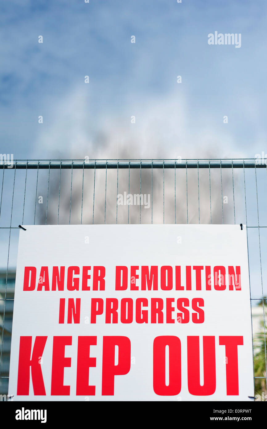 Warning Sign reading 'Danger Demolition in Progress KEEP OUT ' on a construction site with rising smoke - Stock Image