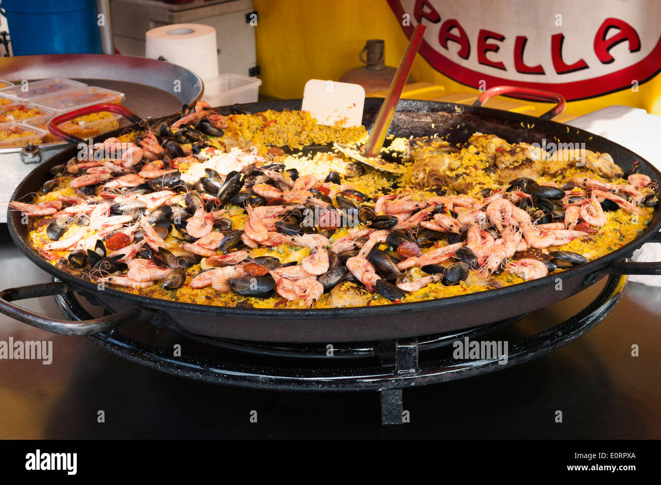 Large dish of Paella on a seafood market stall - Stock Image