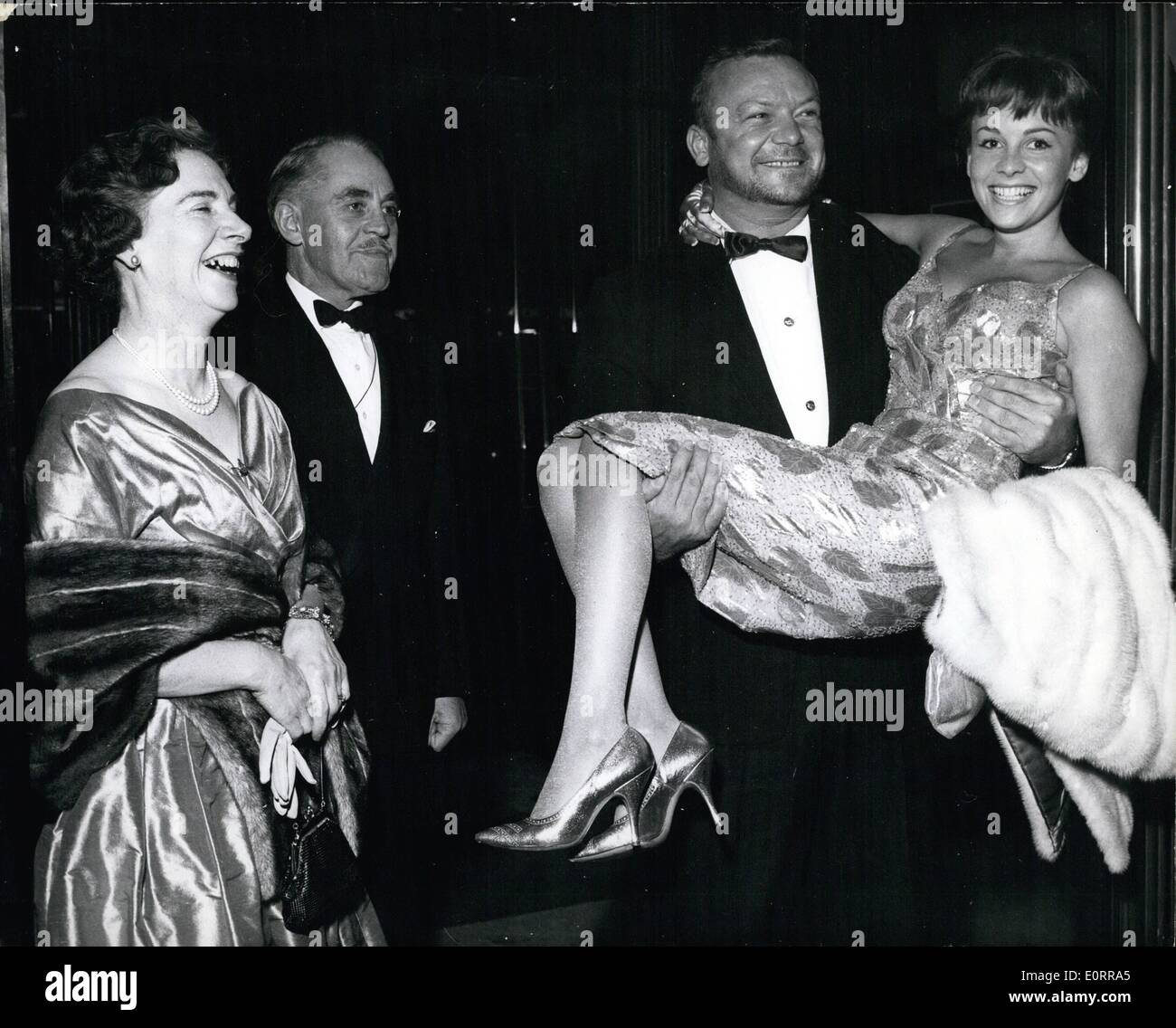 May 05, 1960 - Hollywood ''Tough Guy'' Aldo Ray -accompanied by his English wife-21 year old Johann- his bride of only two months- attended the premier at the Leicester Square Theatre-last evening of his new film- ''The Day they Robbed The Bank of England''. Keystone photo shows: Aldo Ray carries hois yooung bride into the Theatre last night-watched by her parents-Major General Roland and Mrs Bennett... Their (difference'-over the marriage of their daughter-appear to have been resolved amiably. - Stock Image
