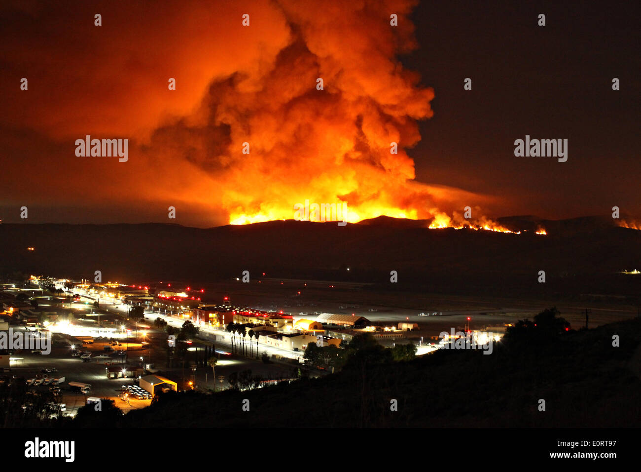 The Las Pulgas and Tomahawk wildfire burns at night in the foothills around the Marine Corps Air Station May 16, 2014 in Camp Pendleton, California. - Stock Image