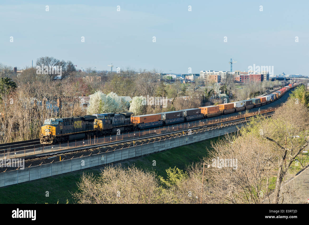 Long freight train pulls along track from Washington DC to Alexandria in Virginia, USA - Stock Image