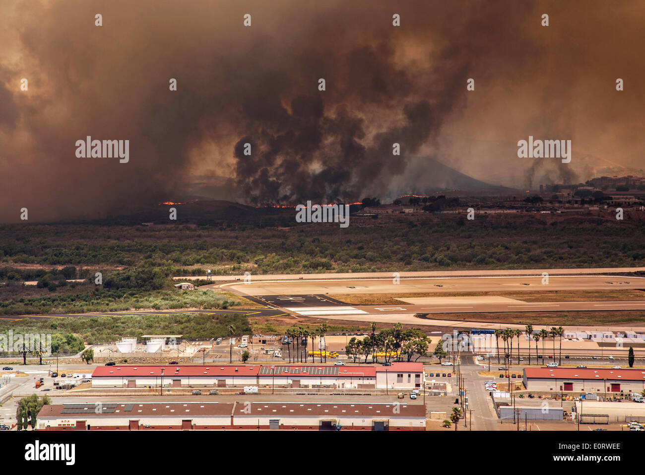 The Las Pulgas wildfire burns along the runway in the foothills around the Marine Corps Air Station May 16, 2014 in Camp Pendleton, California. - Stock Image