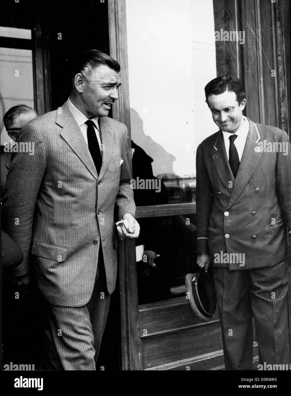 Actor Clark Gable talks with the doorman as he leaves - Stock Image