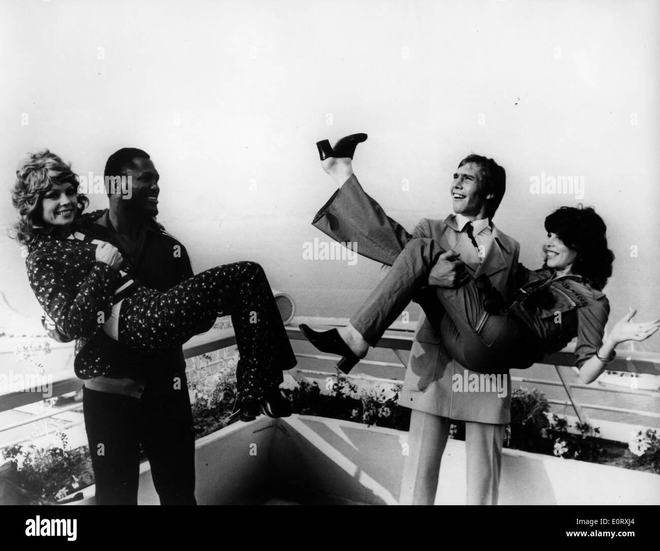 Smokin' Joe Frazier and friend carrying two women - Stock Image