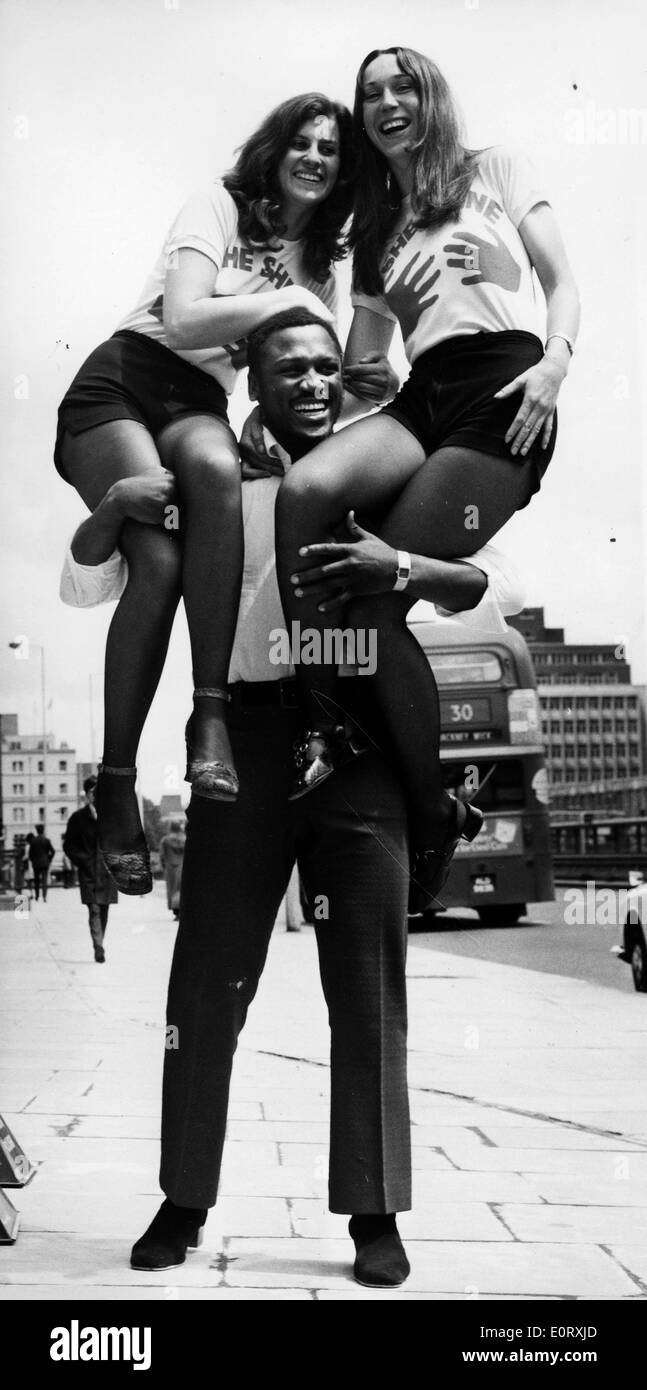 Boxer Smokin' Joe Frazier holding two women on his shoulders - Stock Image