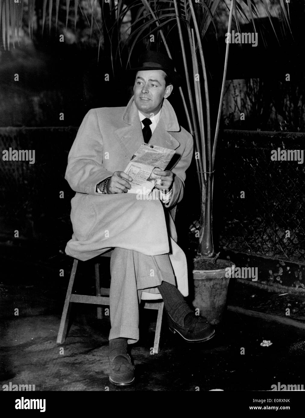 Actor Alan Ladd reads the paper in a film scene - Stock Image