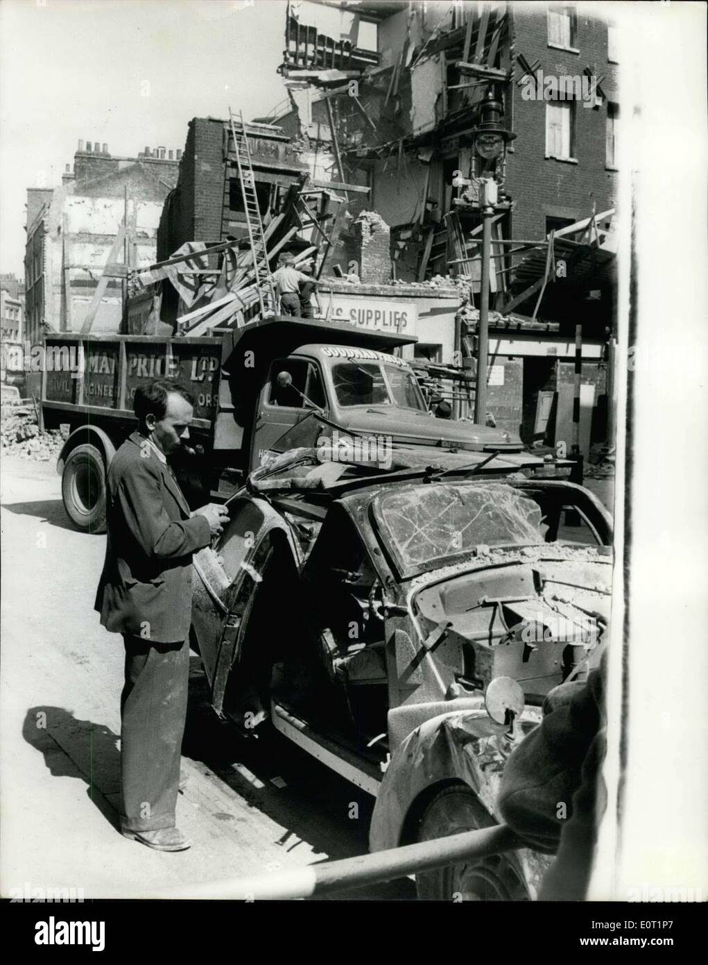 Jul. 06, 1960 - Shop Collapses And Wrecks Pre-War Car... Mr. Hugh Walters of Norbury a school-teacher left his 1938 Ford '8' car in Lisle St., Soho, yesterday - while he went to keep an appointment at a Soho hospital.. While he was away building alongside that was under process of demolition - collapsed of its own volition fifty tons of debris crashed down on the car - turning it into a complete wreck.. Luckily no one was hurt. Photo Shows: Mr Hugh Walters looks at the wreckage of his car - after the crash of the building - yesterday. - Stock Image
