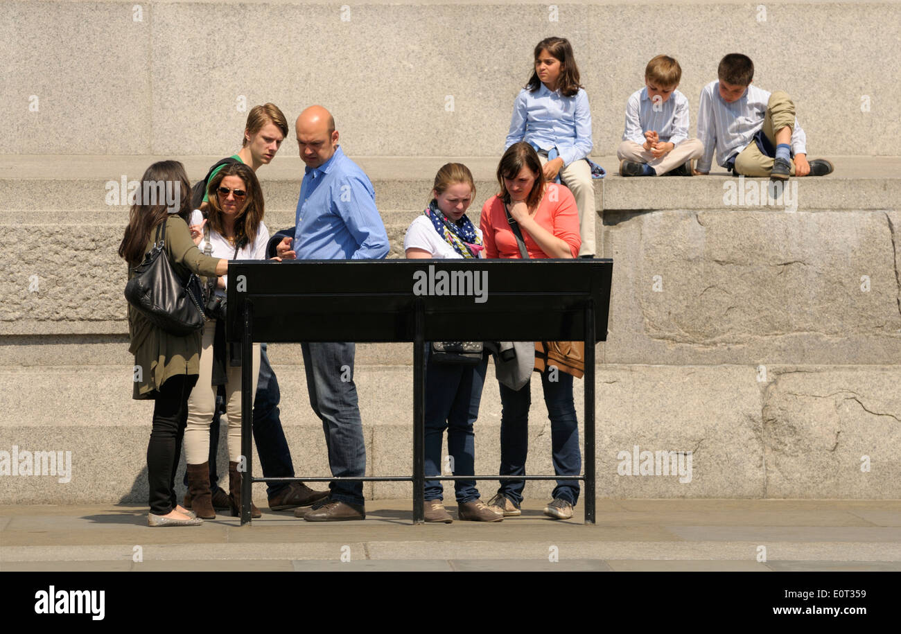 London, England, UK. Family looking at information board by Nelson's Column Stock Photo