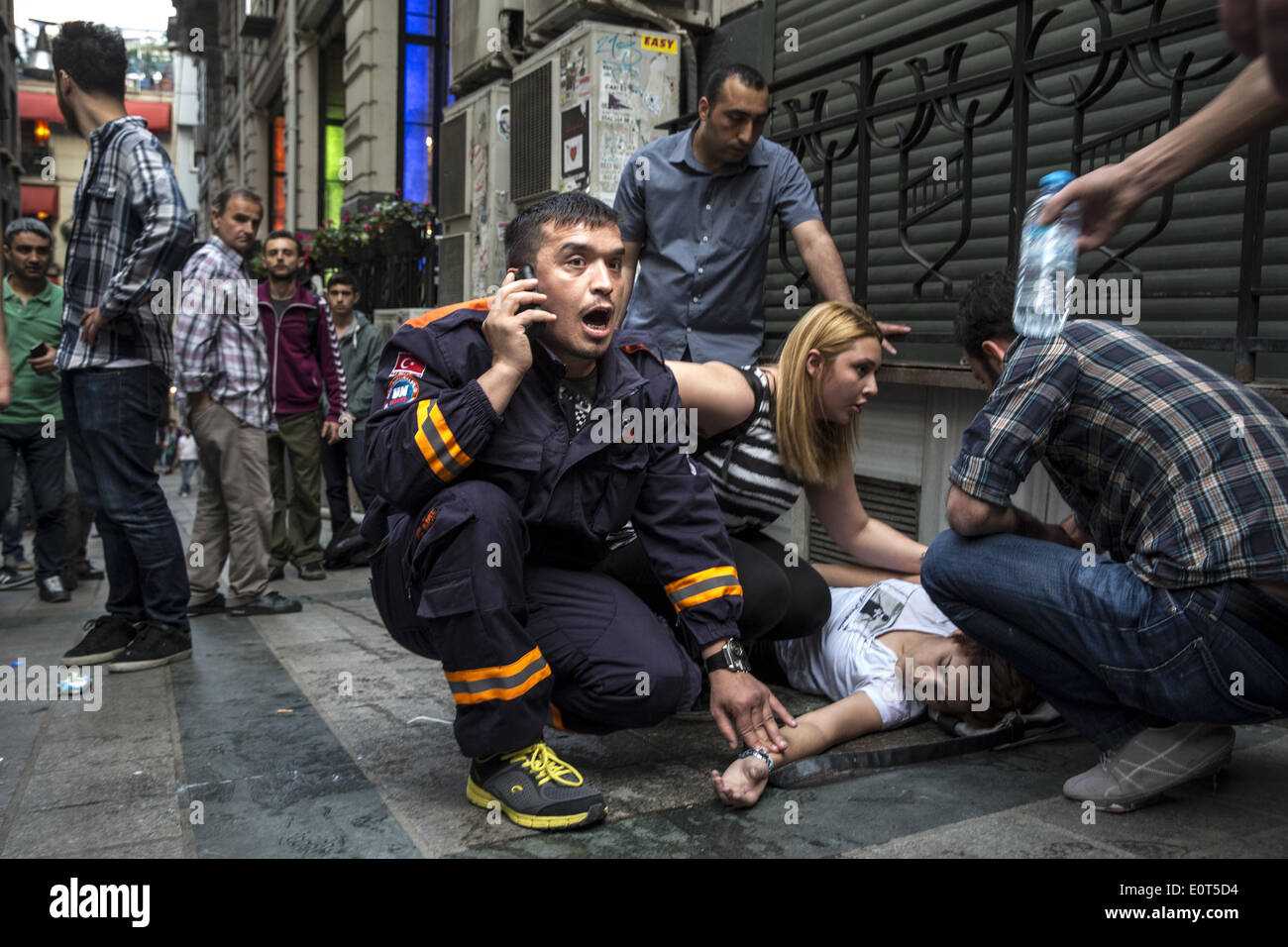 Istanbul, Turkey. 17th May, 2014. A medic calls for help after a girl fell ill and had difficulty breathing when police fired tear gas at protesters on May 17, 2014 in Istanbul. Anger has been mounting across the country regarding the government's handling and responsibility in the Soma mine accident, the worst in Turkey's history, which killed at least 300 miners. PHOTO BY JODI HILTON/NURPHOTO © Jodi Hilton/NurPhoto/ZUMAPRESS.com/Alamy Live News - Stock Image