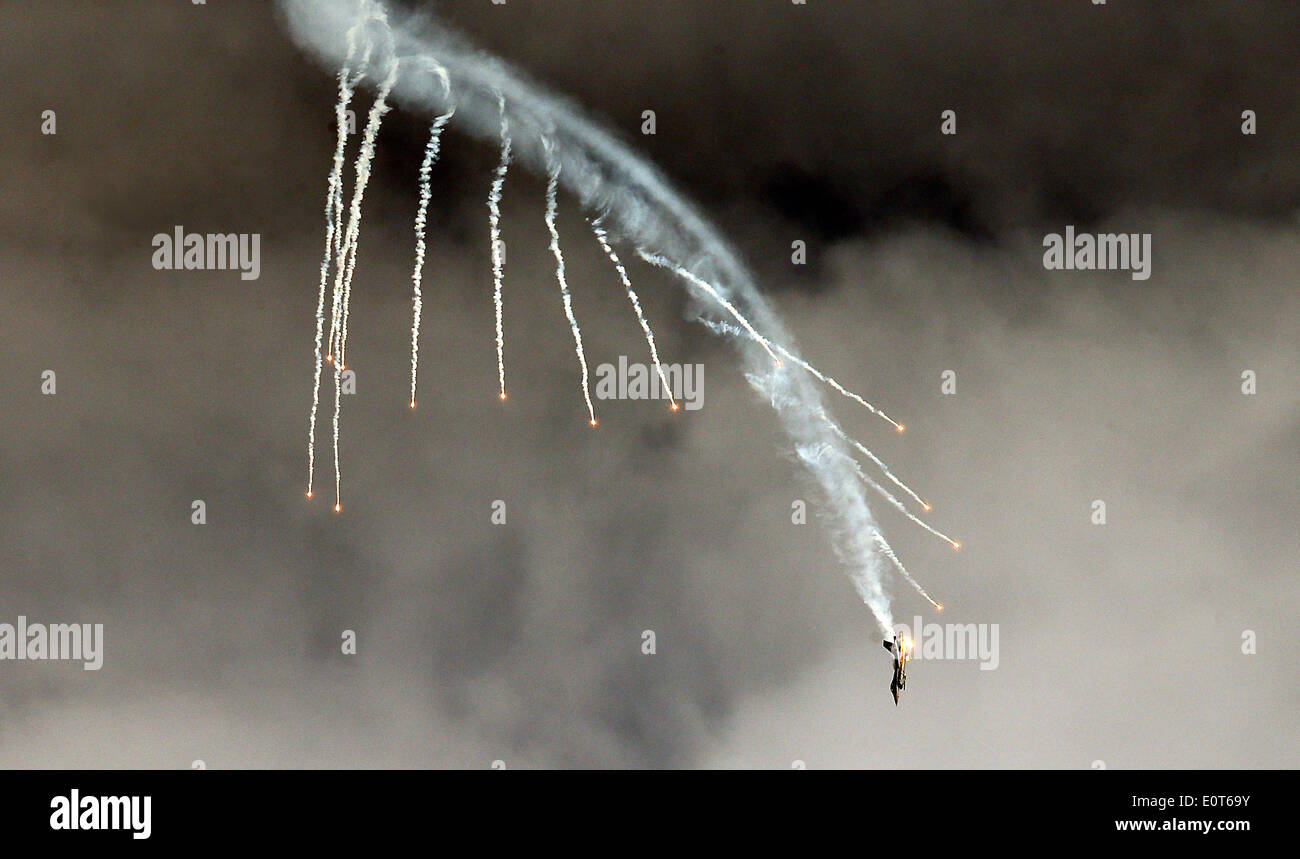 Schoenefeld, Germany. 19th May, 2014. A Lockheed Martin F-16 of the Turkish air force is pictured in flight releasing flares at the the ILA Berlin Air Show at the future Willy Brandt Airport BER in Selchow near Schoenefeld, Germany, 19 May 2014. Ila Berlin Air Show 2014 takes place on the southern area of Berlin-Schoenefeld airport from 20 till 25 May 2014. Photo: WOLFGANG KUMM/DPA/Alamy Live News - Stock Image