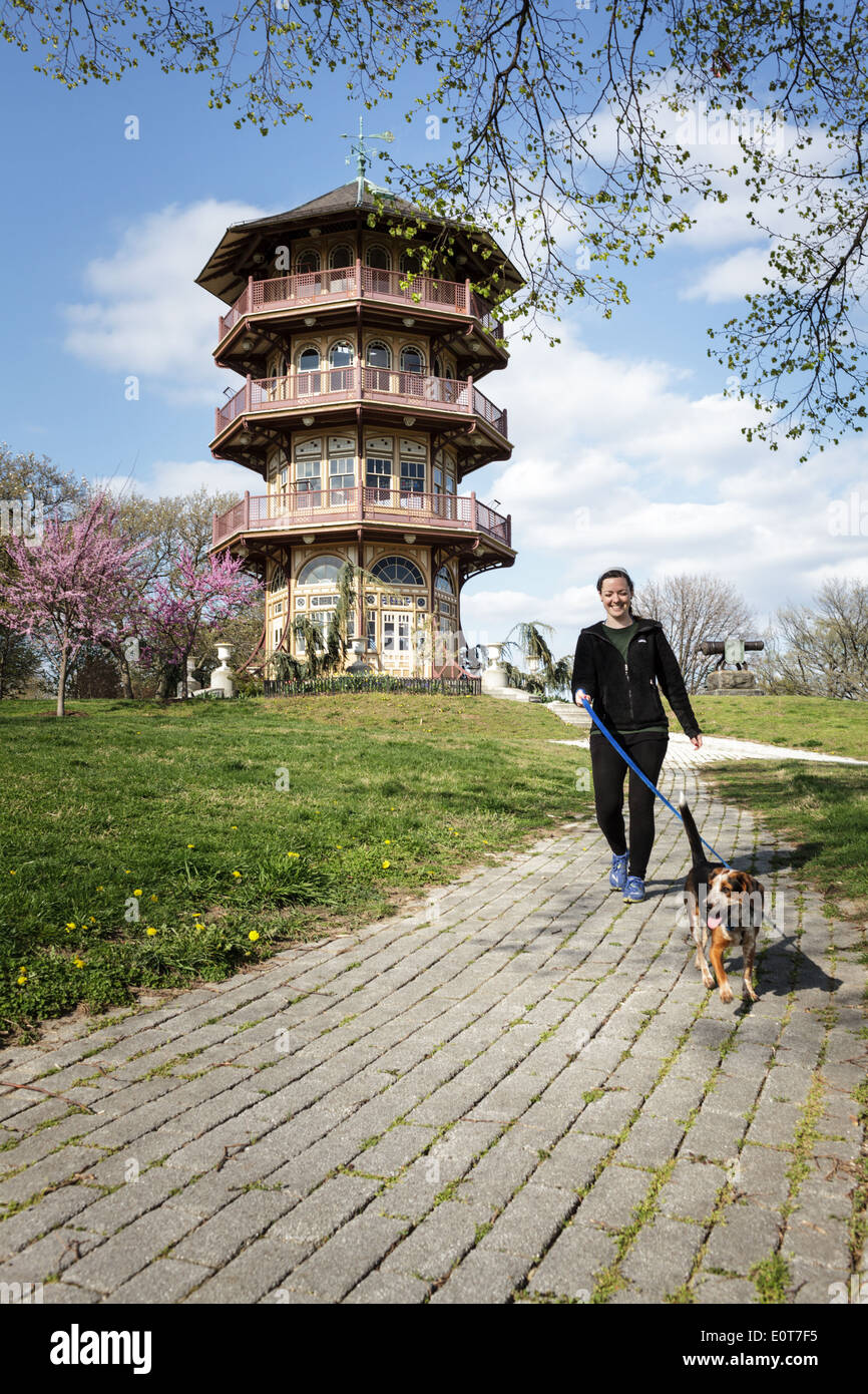 Woman walking her dog by the gazebo at Patterson Park, Baltimore, Maryland, USA - Stock Image