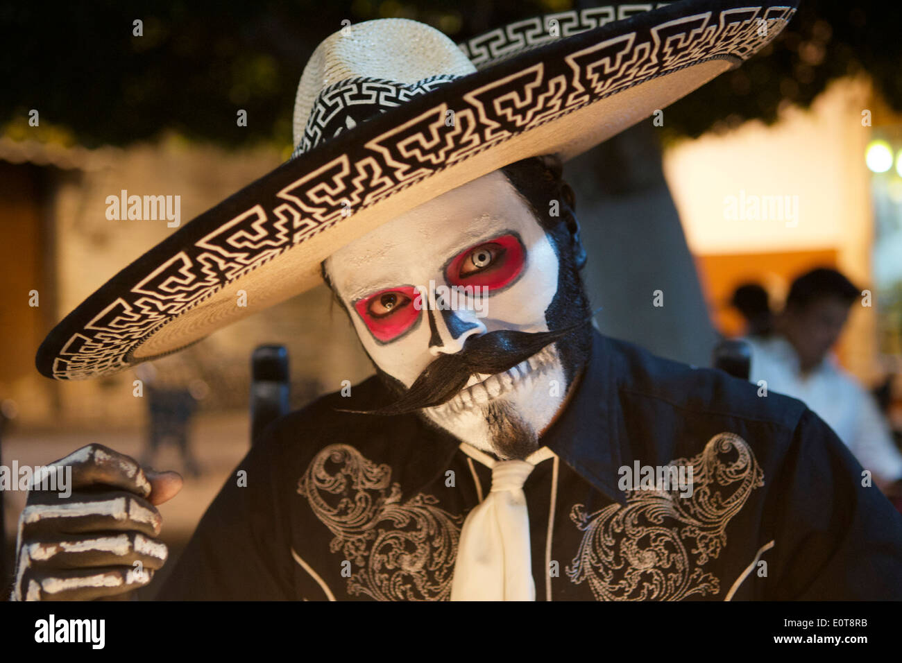 Close-up street mime artist dressed as Day of the Dead skeleton at night Guanajuato Mexico - Stock Image
