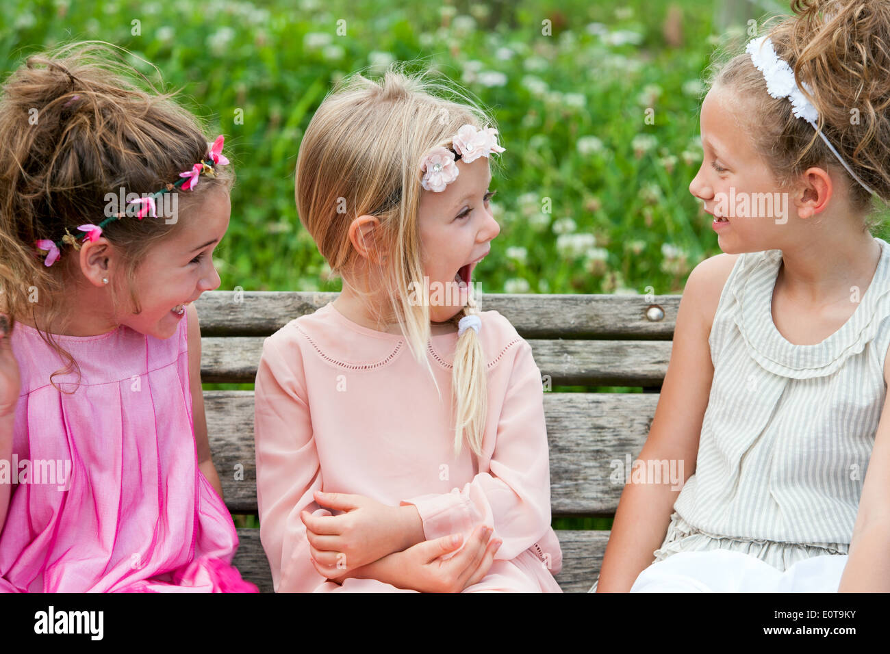 Three cute youngsters on wooden bench having fun. - Stock Image