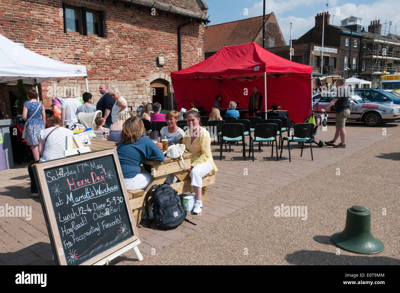 People sitting outside Marriott's Warehouse on the South Quay, King's Lynn, enjoying the sun during the Hanse Festival. - Stock Image