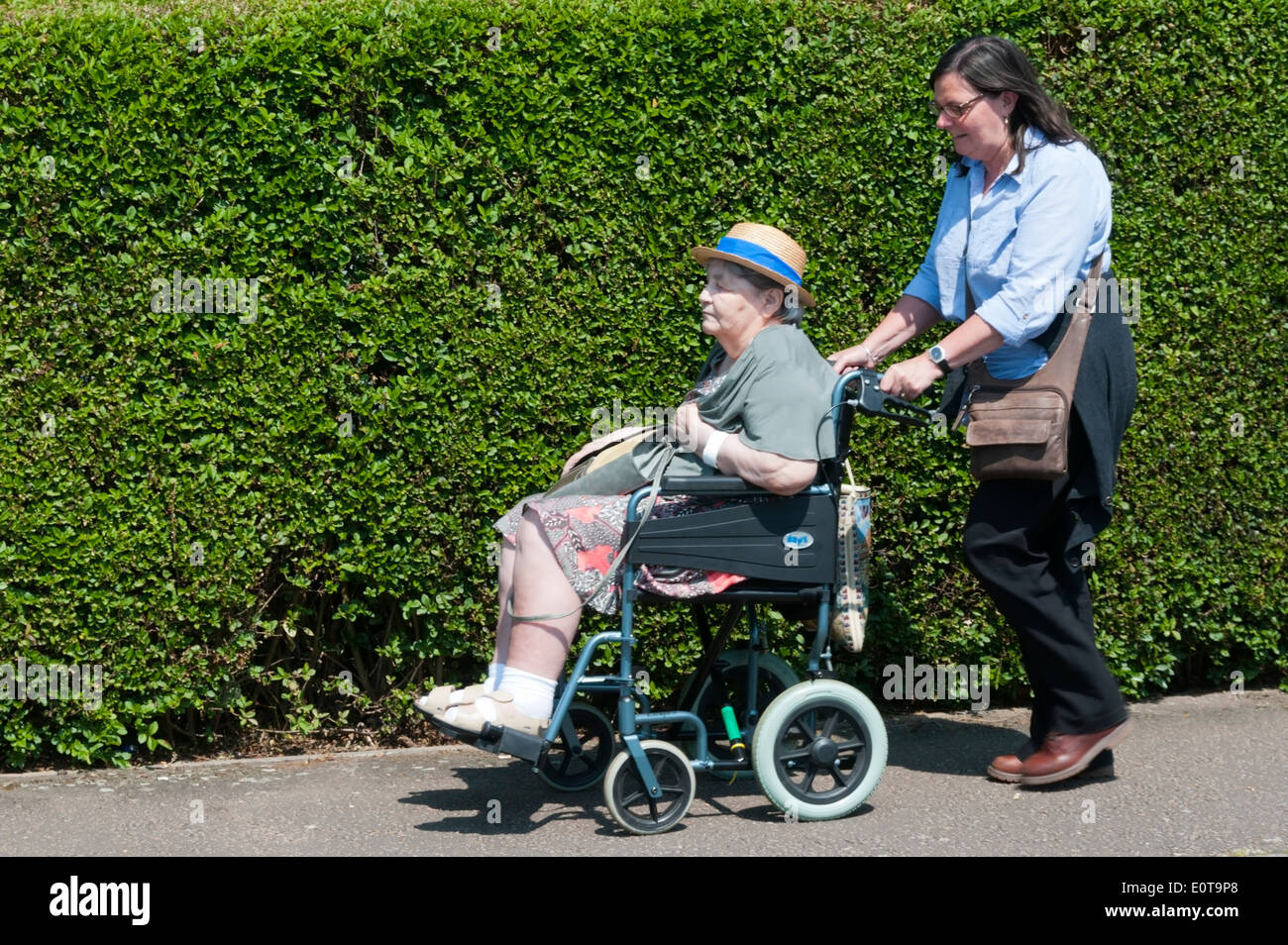 An elderly lady wearing a sun hat is pushed along the pavement in a wheelchair by her carer on a sunny day. - Stock Image