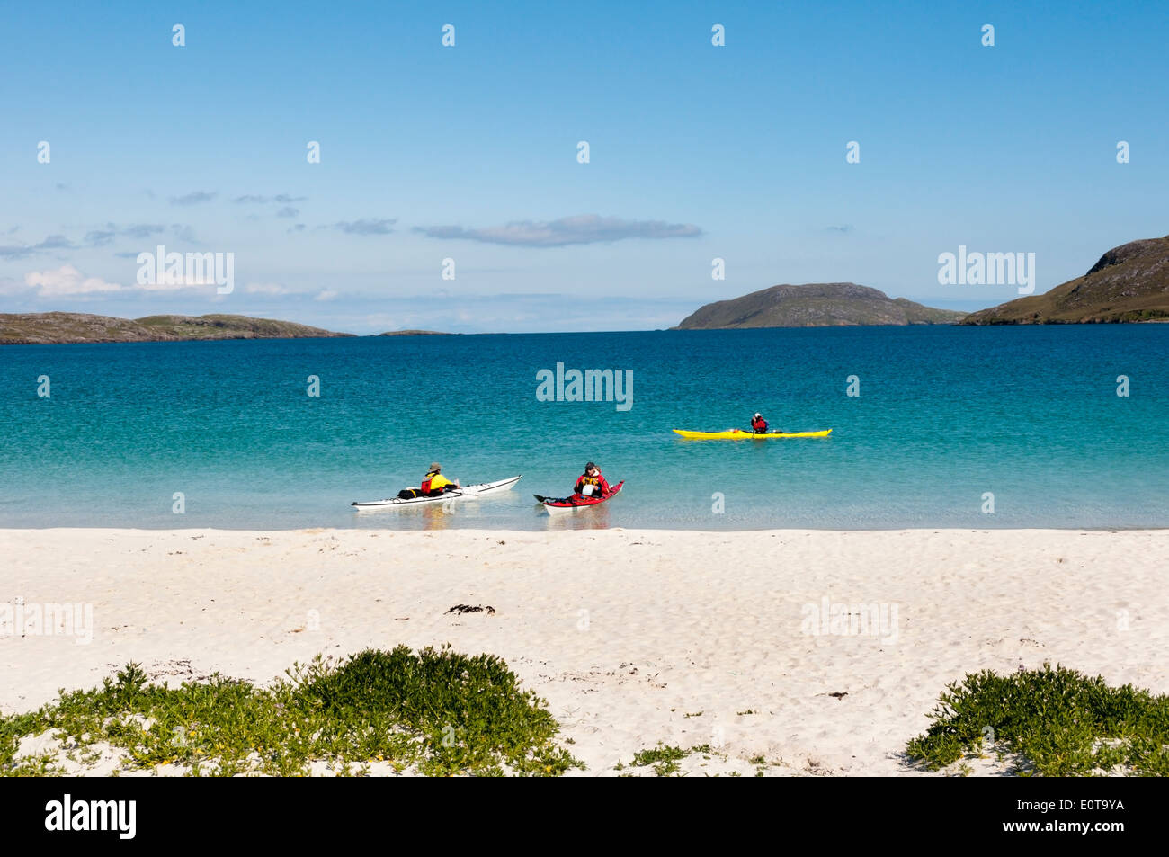 Kayakers paddling along the coast off the east beach of Vatersay in the Outer Hebrides. - Stock Image