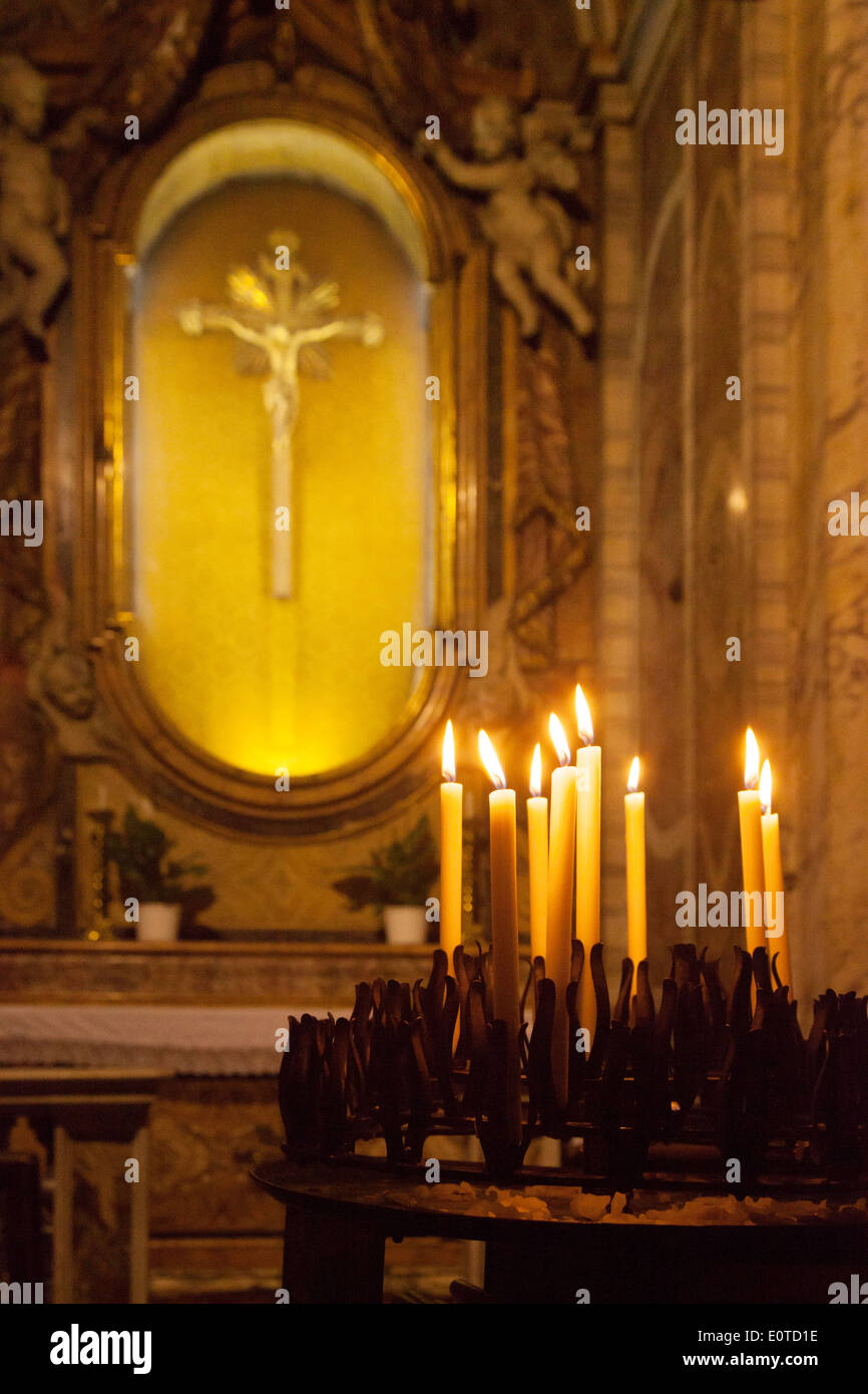 Candles in front of Jesus Christ on the Cross, religious symbols of christianity, Church of St. Mary Magdalene, Rome, Italy - Stock Image