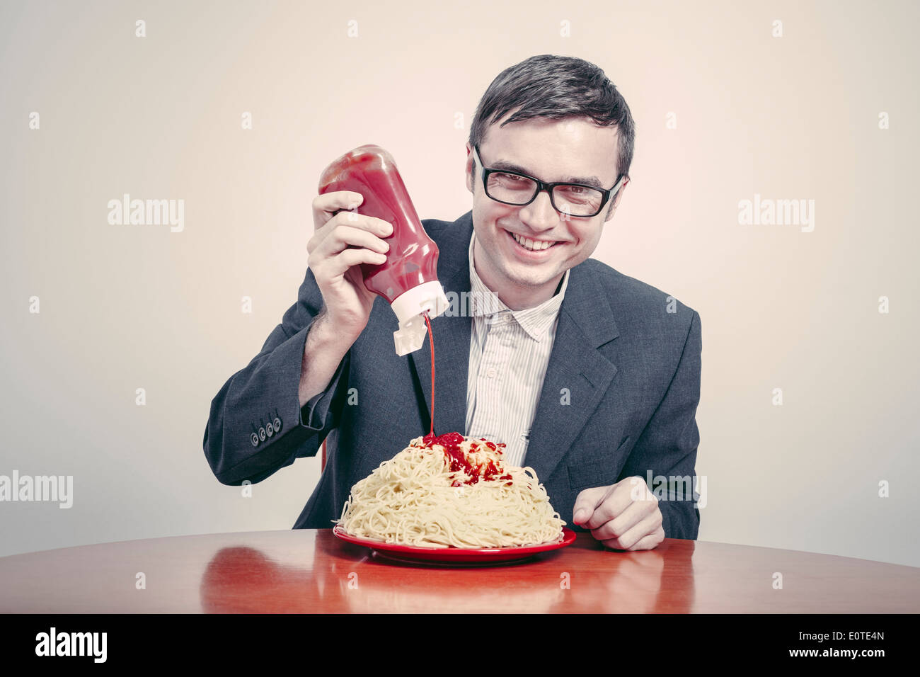 Positive consumerism concept. Happy businessman pouring ketchup on large dish of pasta. - Stock Image