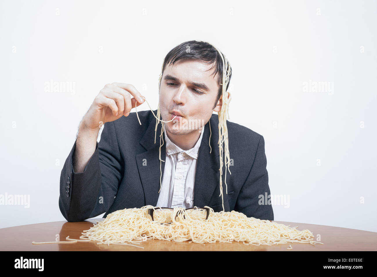Indulgence and consumerism concept. Gluttonous businessman eating pasta. - Stock Image