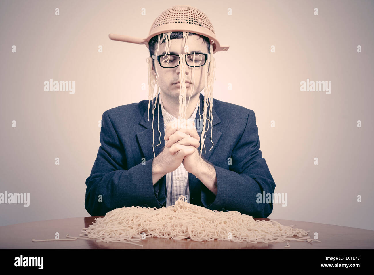 Pastafarian wearing a colander praying for pasta to the Flying Spaghetti Monster. - Stock Image
