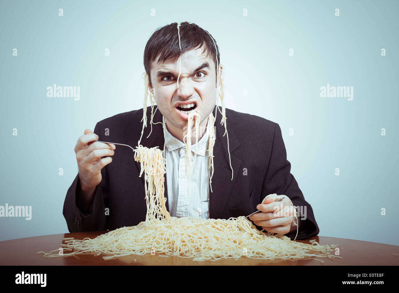 Greedy consumerism concept. Nasty businessman eating pasta on the table. - Stock Image