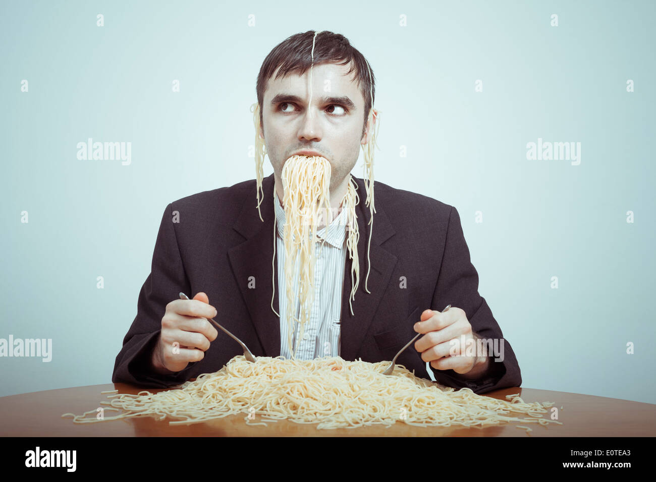 Overeating and consumerism concept. Silly nasty businessman eating pasta. Stock Photo