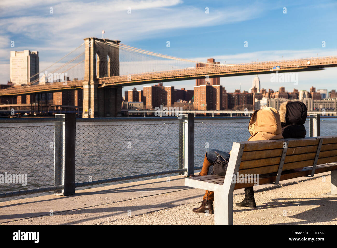 Snug girls sitting in a bench in Brooklyn Heights Park looking to Manhattan and Brooklyn Bridge - Stock Image