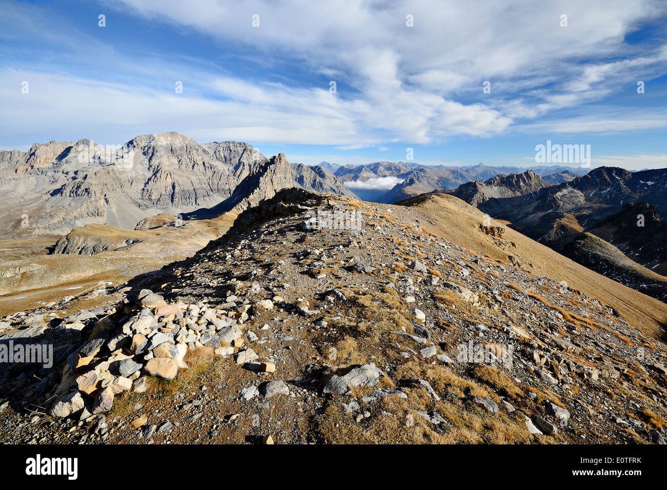 Mountain footpath leading up to the top of M. Thabor (3178 m) in afternoon light on barren terrain. Stock Photo