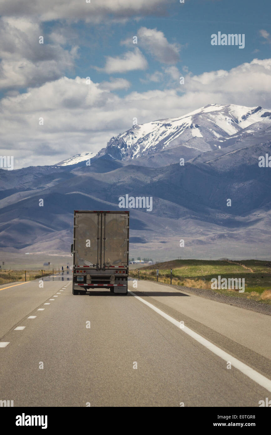 shiping truck on a highway in nevada with spring snow on large tall mountains in the background - Stock Image