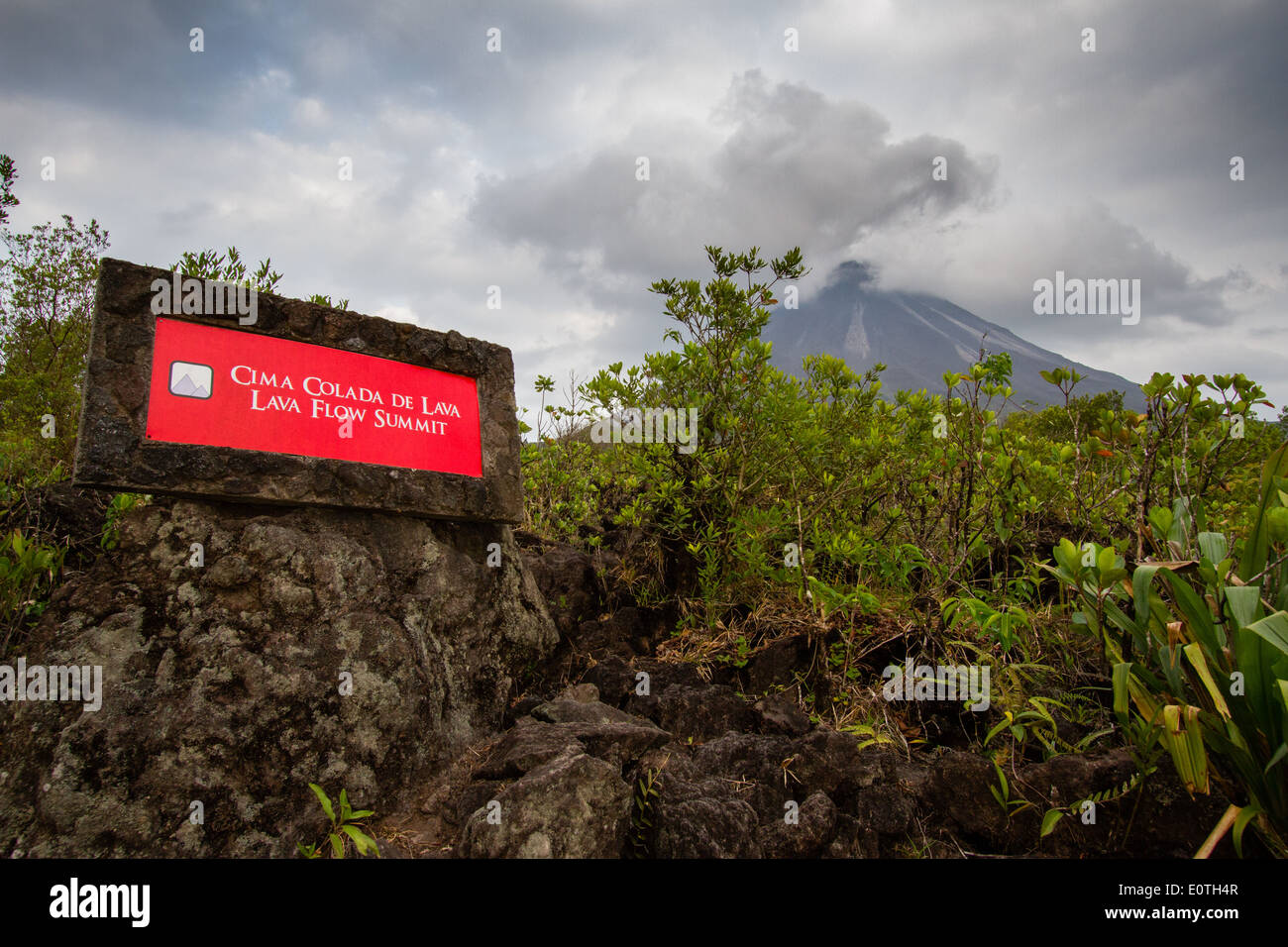 Arenal volcano from the 1968 eruption lava flow - summit marker sign - Costa Rica - Stock Image