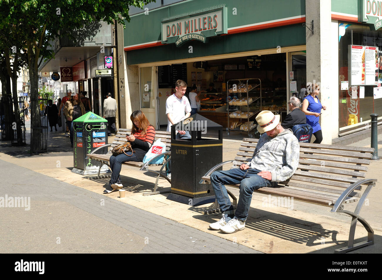 man snoozing on bench in Luton town centre - Stock Image