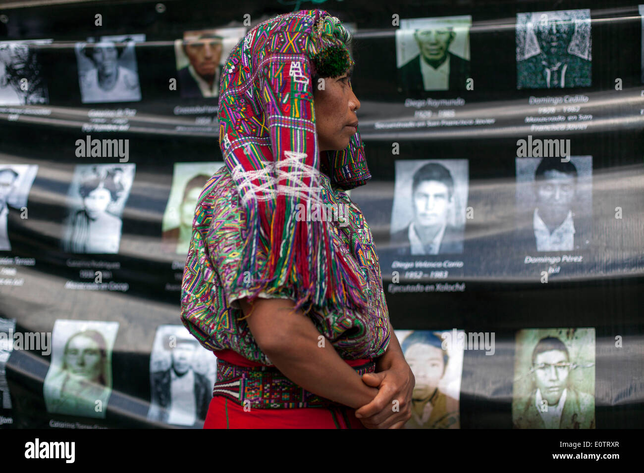 Guatemla City, Guatemala. 19th May, 2014. An indigenous woman of the maya-ixil ethnicity is seen in front of a banner with images of the faces of people that went missing during the Guatemalan internal armed conflcit (1960-1996), during a protest in front of the Legislative Palace, in Guatemala City, capital of Guatemala, on May 19, 2014. Credit:  Luis Echeverria/Xinhua/Alamy Live News - Stock Image