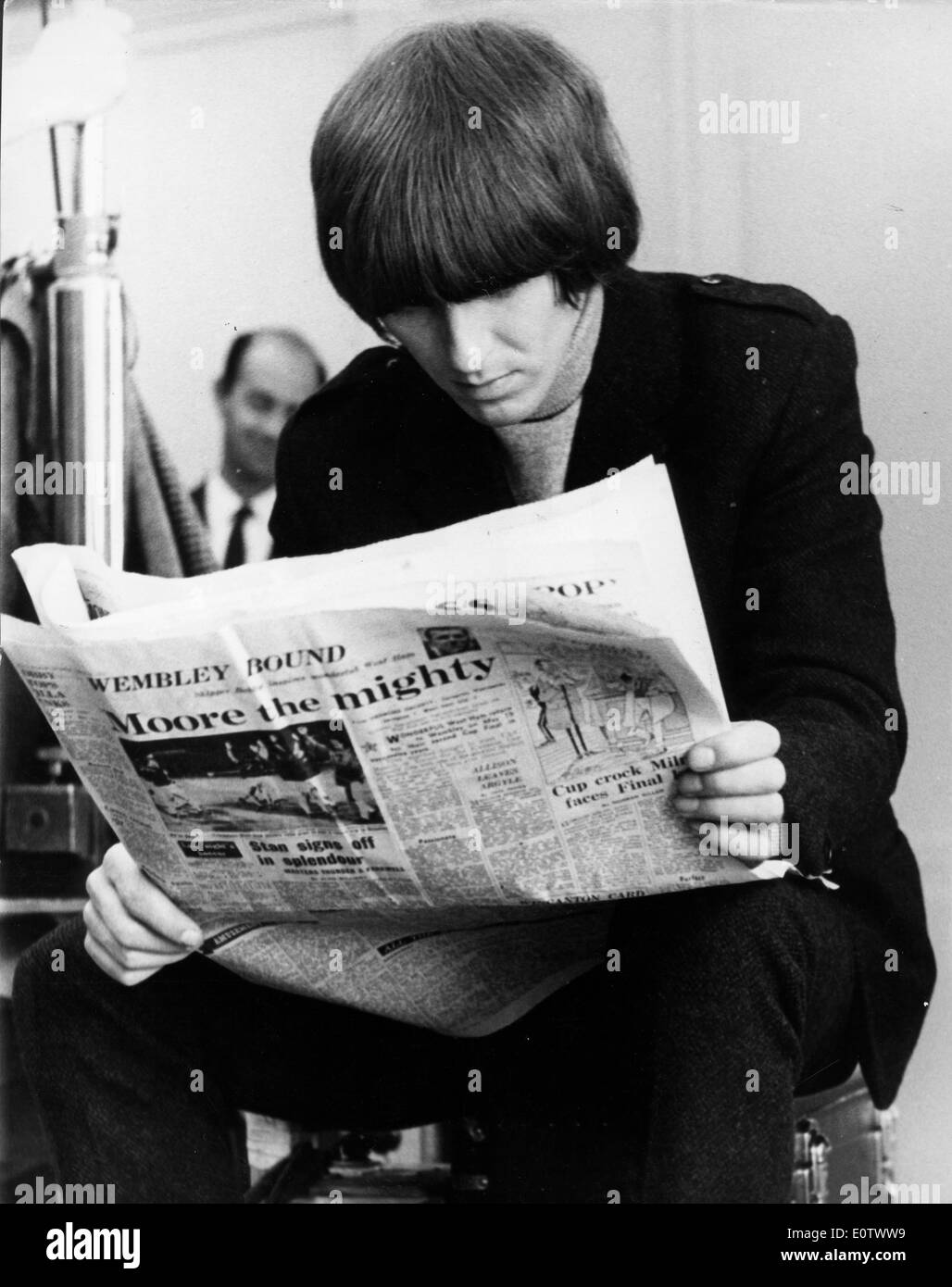 Beatle George Harrison reading a newspaper - Stock Image