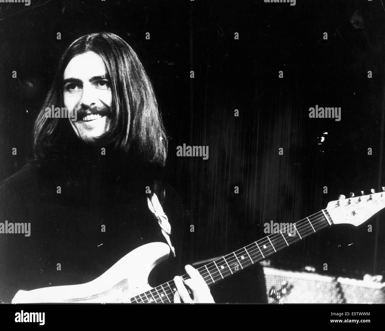 Beatle George Harrison performing during a concert - Stock Image