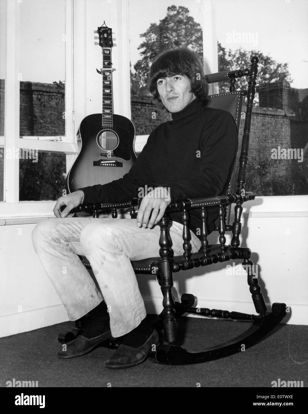 Beatle George Harrison relaxes in rocking chair - Stock Image