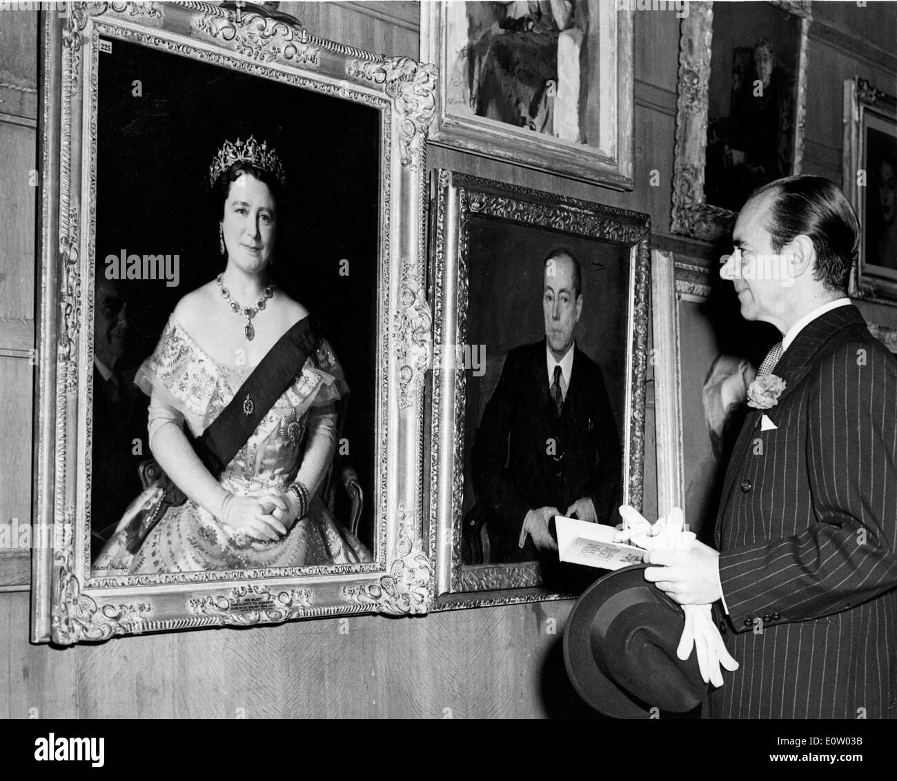 Malcolm Sargent looking at portraits of the Queen - Stock Image