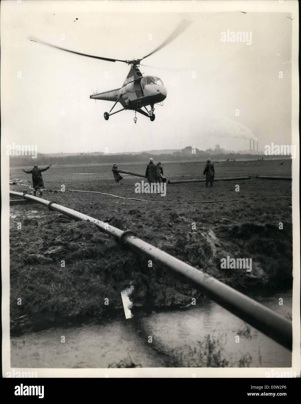 Jan. 01, 1961 - Operation Pipeline. Experiment by Helicopter over the Marshes of Kent.: An experiment was carried out across the Thames marshes at Cliffo, near Gravesond, Kent with the laying of steel pipe-with the aid of a helicopter. Half a mile of 8'' nominal bore stool pipe, made up of 100 flanged lengths - each 20' long and weighing 4 Cwt. The task was carried out by a British United Airways Widgeon - piloted by ex-Navy pilot Mike Perkis. The job - which would normally take ten to fourteen days - was completed today in a matter of hours - Stock Image