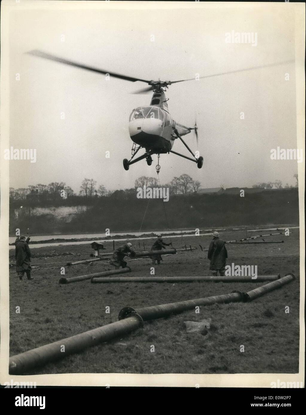 Jan. 01, 1961 - Operation Pipeline. Experiment by Helicopter over the Marshes of Kent.: An experiment was Helicopter carried out across the Thames marshes at Cliffo, near Gravesond, Kent with the laying of steel pipe-with the aid of a helicopter. Half a mile of 8'' nominal bore stool pipe, made up of 100 flanged lengths - each 20' long and weighing 4 Cwt. The task was carried out by a British United Airways Widgeon - piloted by ex-Navy pilot Mike Perkis. The job - which would normally take ten to fourteen days - was completed today in a matter of hours - Stock Image