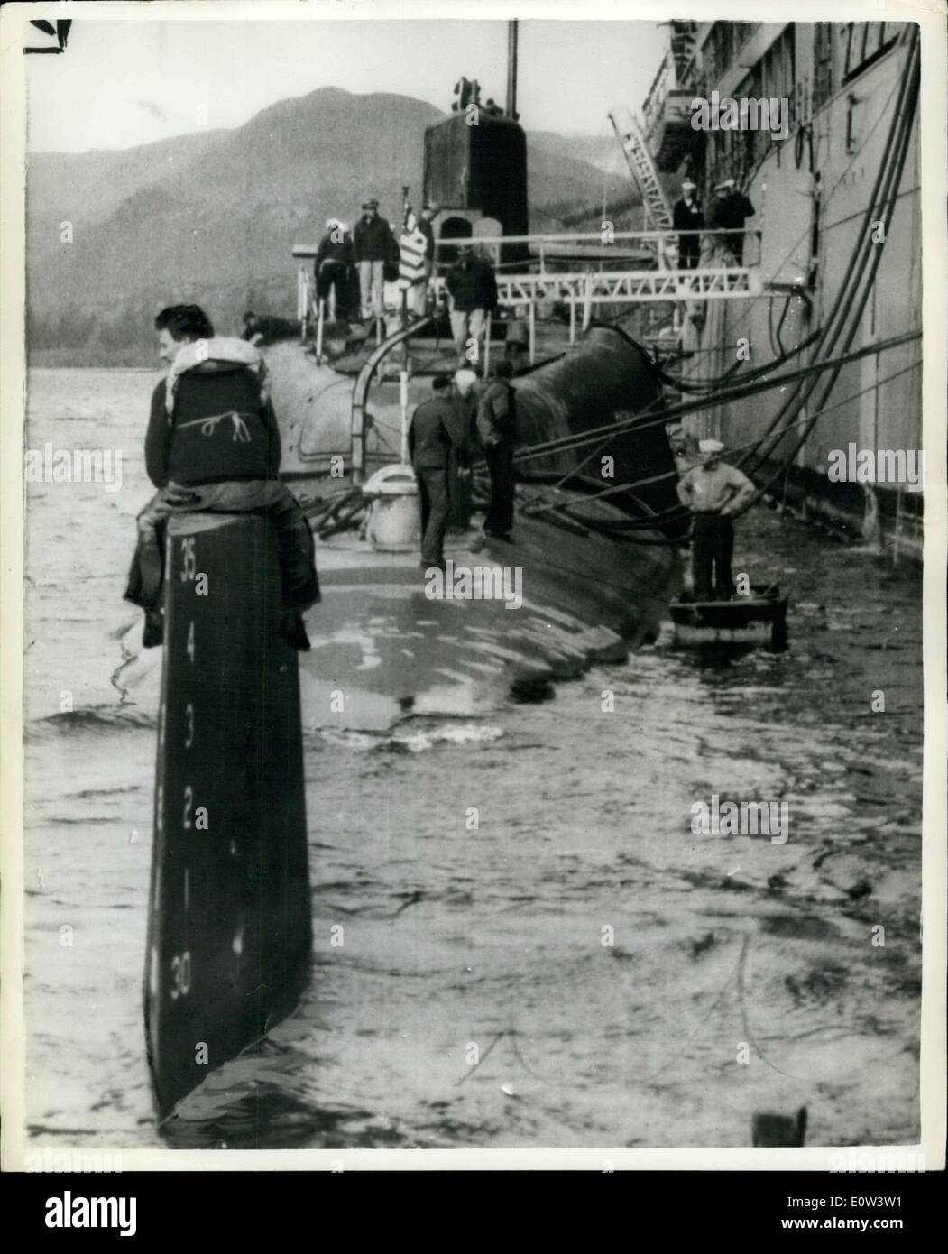 Mar. 28, 1961 - Demonstrator squats on nuclear sub?s tailfin ? An anti-Polaris demonstrator sat above the waves on the tailfin of America?s nuclear submarine ?Patrick Henry? for 45 minutes yesterday in the Holy Loch. He stayed there until he was taken off by police. He was one of the three commandos who boarded the vessel in defiance of warnings to keep clear. One of the men was pulled from a canoe up the side of the submarine by a sailor and then slumped into ?passive resistance? drill. The second went alongside the sub and was pulled aboard, the third sat on the tailfin - Stock Image
