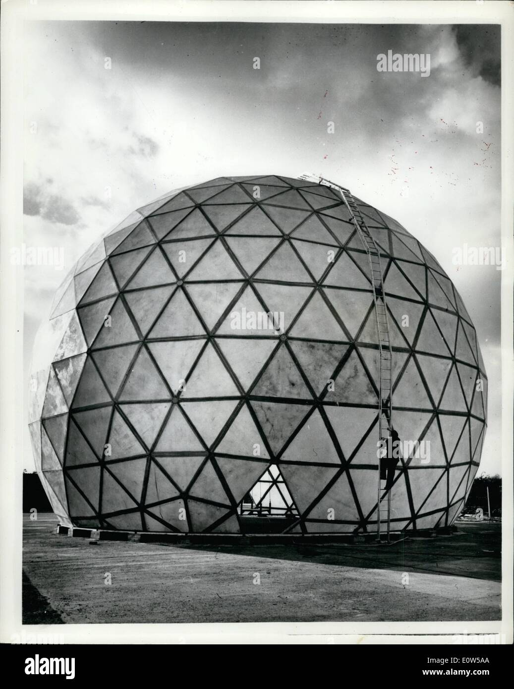 Sep. 09, 1961 - Europe's Largest Reinforced Plastic Structure Completed: The largest reinforced plastics structure yet made in Europe, a ground radome, which looks like a giant three-quarter football, has just been completed and erected for test by English Electric at Freckleton, Lancs. The structure, for the Protection of the defence radar equipment, is designed to Withstand hurricane force winds and temperature well below zero.It is nearly 70 feet in diameter and more than 50 feet high. Photo Shows A workmen climbing a ladder on the redome at Freckleton. - Stock Image